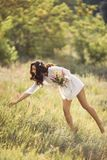 Natural beauty girl with bouquet of flowers outdoor in freedom enjoyment concept. Beautiful young woman in white dress collecting wild flowers at the rural stock photo