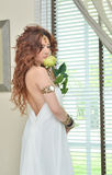 Beautiful young woman in white dress with flower Stock Image