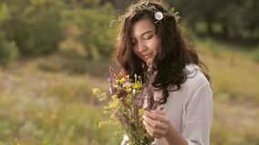 Natural beauty girl with bouquet of flowers outdoor in freedom enjoyment concept. Portrait photo stock footage