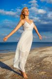 Beautiful young woman in white dress by the sea in the sun stock photo