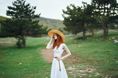 Beautiful young woman in a white dress is standing on a meadow in the mountains Royalty Free Stock Photos