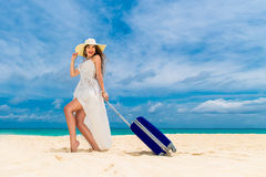 Beautiful young woman in white dress and straw hat with a suitca Royalty Free Stock Photography