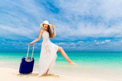 Beautiful young woman in white dress and straw hat with a suitcase. On a tropical beach. Blue sea in the background. Travel concept Royalty Free Stock Photos