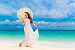 Beautiful young woman in white dress with umbrella on a tropical Royalty Free Stock Photo