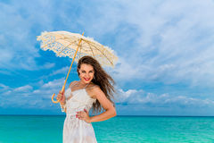 Beautiful young woman in white dress with umbrella on a tropical beach. Blue sea in the background. Travel concept Stock Images