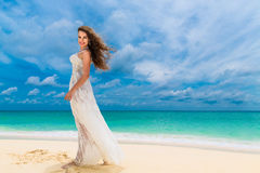 Beautiful young woman in white dress with umbrella on a tropical beach. Blue sea in the background. Travel concept Royalty Free Stock Photos