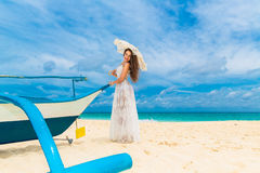 Beautiful young woman in white dress with umbrella on a tropical beach. Blue sea in the background. Travel concept Royalty Free Stock Image