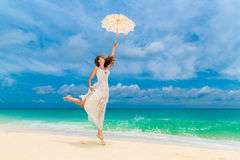 Beautiful young woman in white dress with umbrella on a tropical beach. Blue sea in the background. Travel concept Royalty Free Stock Photography