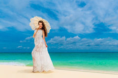 Beautiful young woman in white dress with umbrella on a tropical beach Stock Photos