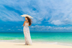 Beautiful young woman in white dress with umbrella on a tropical Stock Images
