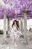 Beautiful young woman in white flying dress over wisteria tunnel stock image