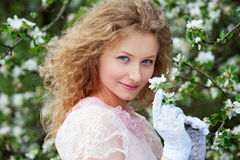 Beautiful young woman in white gloves with flowers Stock Photo