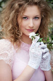 Beautiful young woman in white gloves with flowers Royalty Free Stock Photos