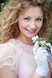 Beautiful young woman in white gloves with flowers Royalty Free Stock Image
