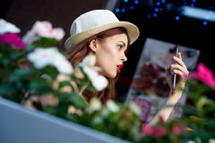Beautiful young woman in white hat doing selfie sitting in cafe on summer street Royalty Free Stock Photos