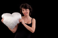 Beautiful young woman with a white heart in hand Royalty Free Stock Photo