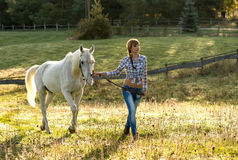 Beautiful young woman with a white horse in the country Stock Images
