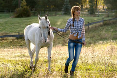 Beautiful young woman with a white horse in the country Royalty Free Stock Image