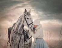 Beautiful young woman with white horse at winter