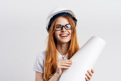 Beautiful young woman on white isolated background holds blueprints, engineer Royalty Free Stock Images