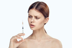 Beautiful young woman on white isolated background holds a syringe, plastic, medicine Royalty Free Stock Photos