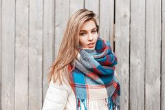 Beautiful young woman in a white jacket with a bright scarf. Near a gray wooden wall stock images