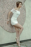 Beautiful young woman in white lace dress posing outdoors. Stock Image