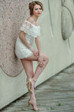 Beautiful young woman in white lace dress posing outdoors. Royalty Free Stock Images