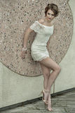 Beautiful young woman in white lace dress posing outdoors, street fashion. Royalty Free Stock Photography