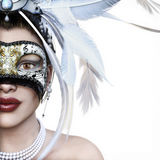 Beautiful young woman in white mysterious Venetian mask on a white background with room for text or copy space Royalty Free Stock Photo