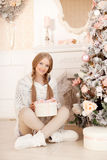 Beautiful young woman in white near the Christmas tree. Beautifu Stock Image
