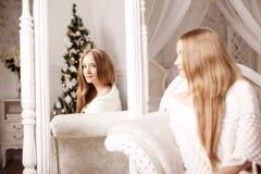 Beautiful young woman in white near the Christmas tree. Beautifu Stock Photo