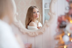 Beautiful young woman in white near the Christmas tree. Beautifu Stock Photos