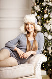 Beautiful young woman in white near the Christmas tree. Beautifu Royalty Free Stock Photo