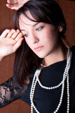 Beautiful  young woman  with white pearl posing. Studio shot Stock Image