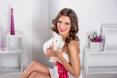 Beautiful young woman with white rabbit in the studio Royalty Free Stock Images