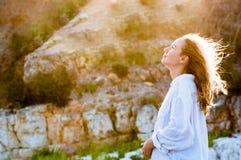 Beautiful young woman in white shirt enjoying sunset light Stock Photo