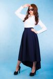 Beautiful young woman in a white shirt and a long blue skirt Stock Photography