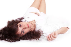 Beautiful young woman in white shirt lying on a Royalty Free Stock Image