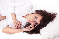 Beautiful young woman in white shirt lying on a Stock Images