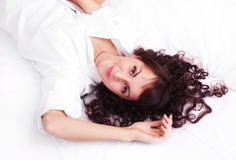 Beautiful young woman in white shirt lying on a Stock Image