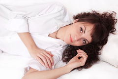 Beautiful young woman in white shirt lying on a Stock Photo