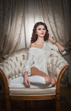 Beautiful young woman in white sitting on sofa posing provocatively in boudoir scenery. Attractive brunette girl with long hair Stock Image