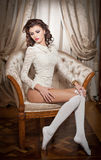 Beautiful young woman in white sitting on sofa posing provocatively in boudoir scenery. Attractive brunette girl with long hair Royalty Free Stock Images