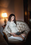 Beautiful young woman in white sitting on sofa working on laptop in boudoir scenery. Attractive brunette girl with long hair Stock Photos