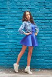 Beautiful young woman in a sneakers on a blue brick wall background royalty free stock photos