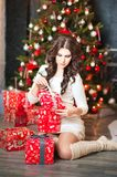 A beautiful young woman in a white sweater dress unpacks New Year`s presents against the backdrop of a New Year tree. Brunette in royalty free stock photos