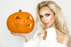 Beautiful young woman in white sweater, standing on white background. And holding pumpkin Royalty Free Stock Photo