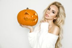 Beautiful young woman in white sweater, standing on white background. And holding pumpkin Stock Images