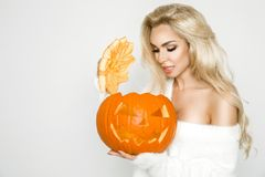 Beautiful young woman in white sweater, standing on white background. And holding pumpkin Stock Photos